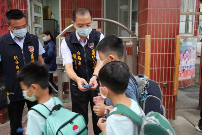 圖片說明:蘆竹分局長陳清華(右)與副分局長高海源(左)在校門前迎接學童。(記者宋紹誠翻攝)
